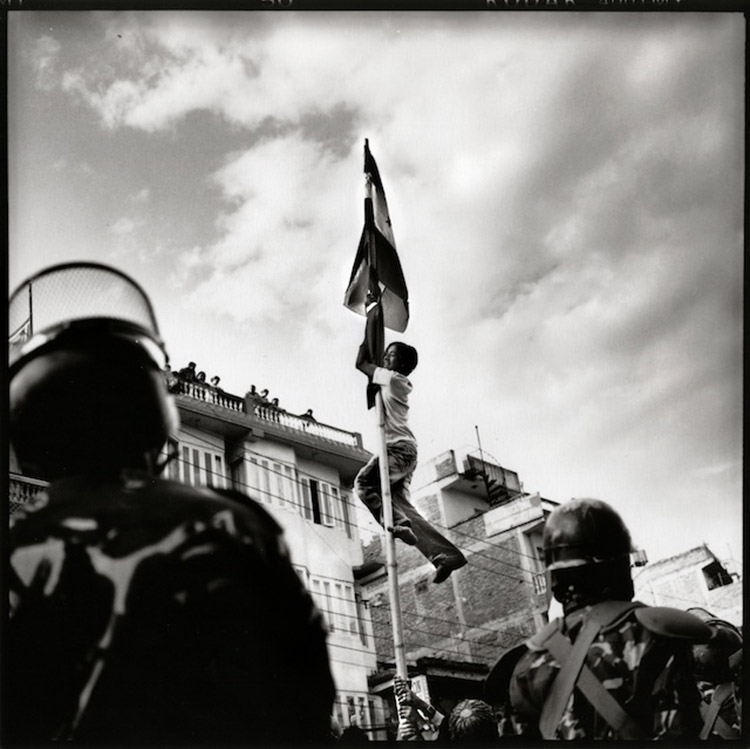 A Demonstrator climbs a flag pole and hangs over police lines at a mass rally aimed at pressuring King Gyanendra to step down in Chabahil on the Kathmandu ring-road. Thursday 19th April 2006