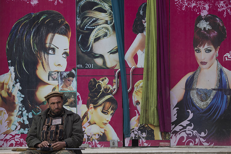 An Afghan security looks on as he sit in front of a barber shop just out of the Kabul-Dubai wedding hall during a ceremony to mark the International Woman's day, in Kabul, March 8, 2014. Despite decades of conflict in Afghanistan, and several recent militant attacks, the country's capital Kabul is home to a vibrant youth scene of musicians, artists, athletes and activists. Shopping malls and cafes stand in the city, which is nonetheless beset by infrastructure problems and instability. Afghanistan is preparing for an election on April 5 that should mark the first democratic transfer of power in the country's history, but it has been hit by a tide of violence as the Islamist Taliban movement has ordered its fighters to disrupt the vote and threatened to kill anyone who participates.
