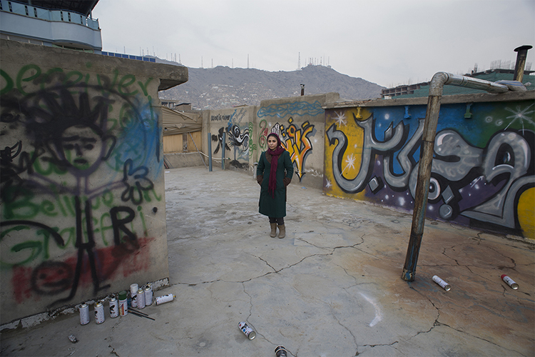 Afghan female artist, Shamsia Hassani, poses for a photograph on a roof of her grafitti workshop in Kabul, March 2, 2014. Despite decades of conflict in Afghanistan, and several recent militant attacks, the country's capital Kabul is home to a vibrant youth scene of musicians, artists, athletes and activists. Shopping malls and cafes stand in the city, which is nonetheless beset by infrastructure problems and instability. Afghanistan is preparing for an election on April 5 that should mark the first democratic transfer of power in the country's history, but it has been hit by a tide of violence as the Islamist Taliban movement has ordered its fighters to disrupt the vote and threatened to kill anyone who participates.