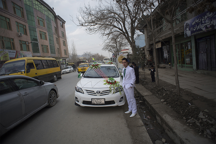 An Afghan groom stands next to his decorated car as he pose for a photograph just after leaving a barber shop in Kabul, March 6, 2014. Despite decades of conflict in Afghanistan, and several recent militant attacks, the country's capital Kabul is home to a vibrant youth scene of musicians, artists, athletes and activists. Shopping malls and cafes stand in the city, which is nonetheless beset by infrastructure problems and instability. Afghanistan is preparing for an election on April 5 that should mark the first democratic transfer of power in the country's history, but it has been hit by a tide of violence as the Islamist Taliban movement has ordered its fighters to disrupt the vote and threatened to kill anyone who participates.
