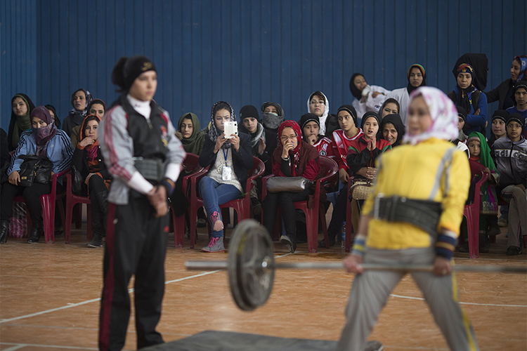 An Afghan female powerlifter performs during a local sport ceremony in a stadium in Kabul, March 8, 2014. Despite decades of conflict in Afghanistan, and several recent militant attacks, the country's capital Kabul is home to a vibrant youth scene of musicians, artists, athletes and activists. Shopping malls and cafes stand in the city, which is nonetheless beset by infrastructure problems and instability. Afghanistan is preparing for an election on April 5 that should mark the first democratic transfer of power in the country's history, but it has been hit by a tide of violence as the Islamist Taliban movement has ordered its fighters to disrupt the vote and threatened to kill anyone who participates.