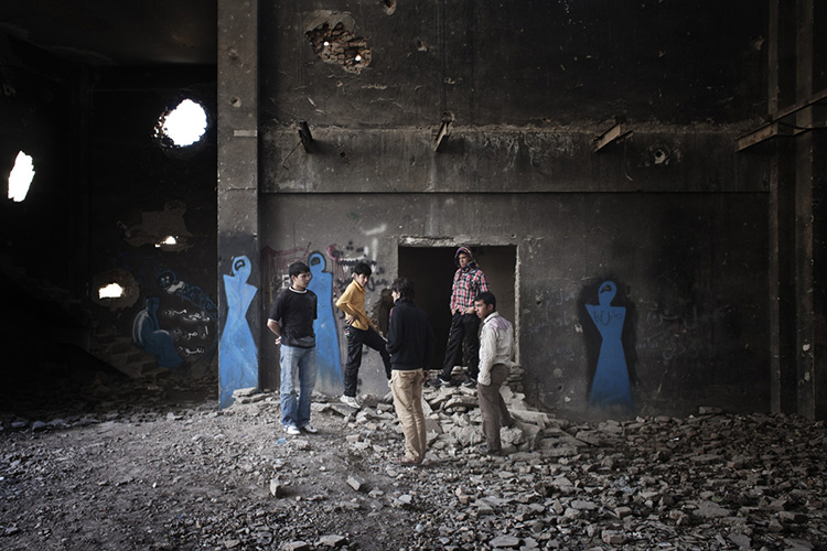 Young men gather in the ruins of the Russian Cultural Centre in Kabul, with the artist Shamsia Hassani's graffiti painted on the walls behind them. 2012