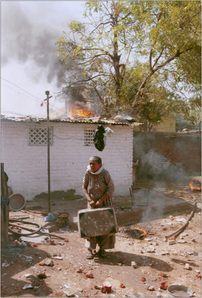 An old muslim woman tries to save her belongings at the Municipality Juna Quarters, a predominantly muslim area, after an angry Hindu mob set her house to fire in Ahmedabad, Gujrat. Clashes between the majority Hindus and minority Muslim communities have complete stopped normal life the city for the last few days.1/3/2002