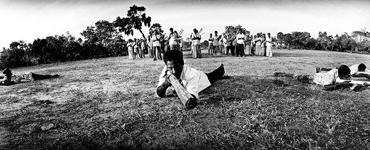#04          © Q. Sakamaki Tamil civilians take military training in Kilinochchi, a stronghold of the rebels. Sticks and branches are used instead of guns, however rebels have distributed firearms to the civilian population. Sri Lanka, June 13, 2006.