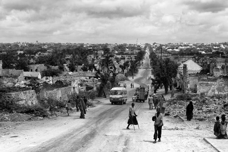 A disable man who lost his leg in war along others walks at a street in Mogadishu, Somalia