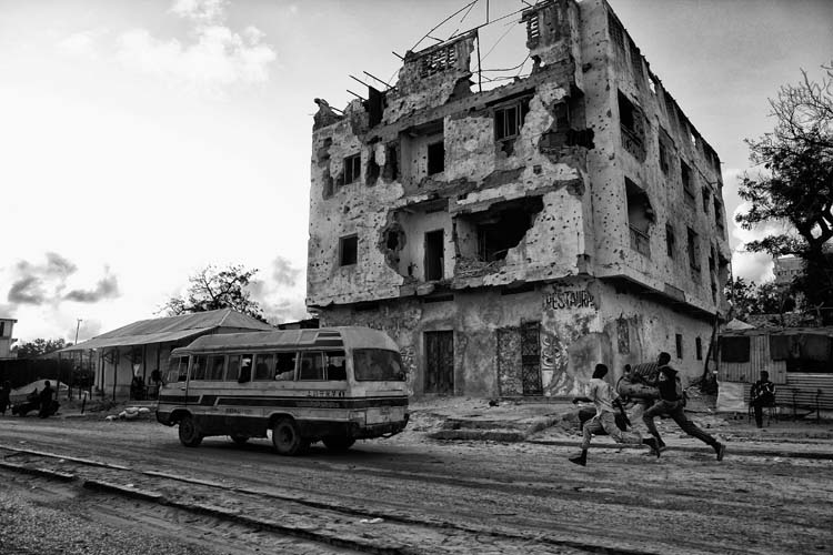 Somali boys run to catch a bus in a civil war damaged area in the city of Mogadishu, Somalia