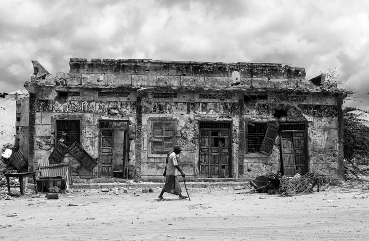 A Somali man passes a building which damaged during civil war in the city of Mogadishu, Somalia