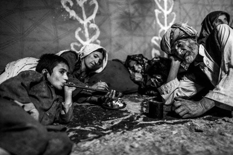 An Afghan boy is smoking opium with his family in Badakhshan