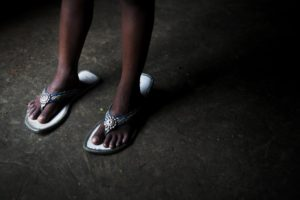 The sandals Felani was supposed to wear in her wedding, now used by her 3 year old sister as a plaything.